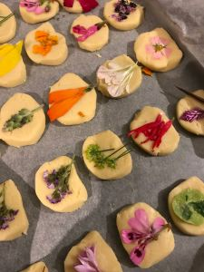 Edible flowers being attached to biscuits with egg white